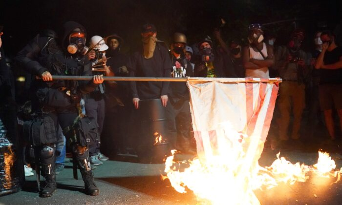 A demonstrator burns an American flag in front of the Mark O. Hatfield Courthouse in the early morning in Portland, Ore., on Aug. 1, 2020. (Nathan Howard/Getty Images)