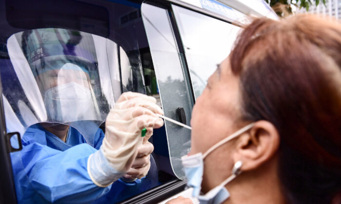 A health worker carries out a COVID-19 coronavirus test on a resident in a testing vehicle in Shenyang in China's northeastern Liaoning Province, China, on July 29, 2020. (STR/AFP via Getty Images)