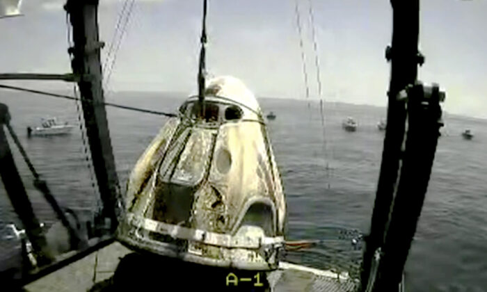 The SpaceX capsule is lifted onto a ship, in the Gulf of Mexico, on Aug. 2, 2020. (NASA TV via AP)