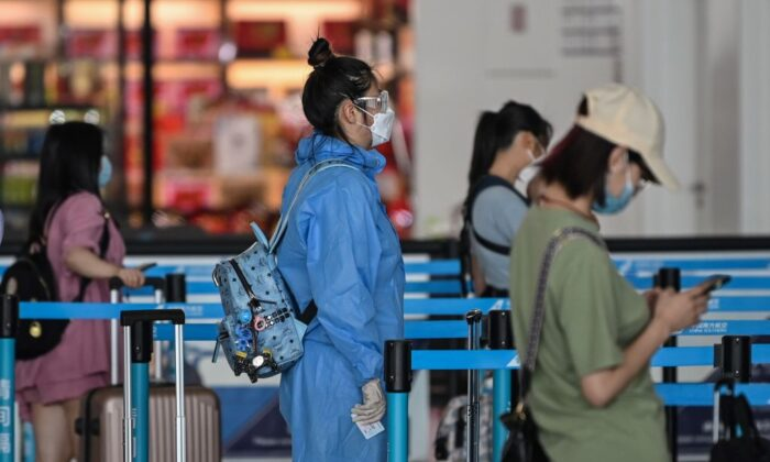 A passenger wearing protective gear and a mask waits in line at an airline counter at Tianhe airport in Wuhan, in central China's Hubei Province, on May 23, 2020. (Hector Retamal/AFP via Getty Images)