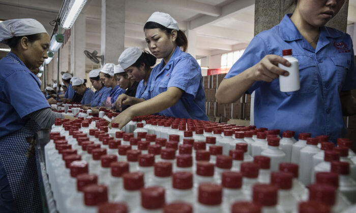 Chinese workers arrange bottles of locally made- baijiu liquor in Maotai, Guizhou province, China, on Sept. 22, 2016. (Kevin Frayer/Getty Images)