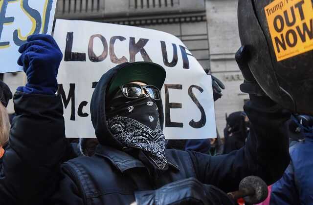 """A protester wearing Antifa's typical """"black bloc"""" style in New York City on Nov. 16, 2019. (Stephanie Keith/Getty Images)"""