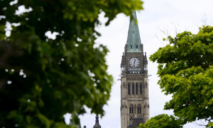 The Peace Tower is seen through the trees on Parliament Hill on July 20, 2020. Recipients of the Canada Emergency Response Benefit will be transferred to a revamped employment insurance system. (The Canadian Press/Sean Kilpatrick)