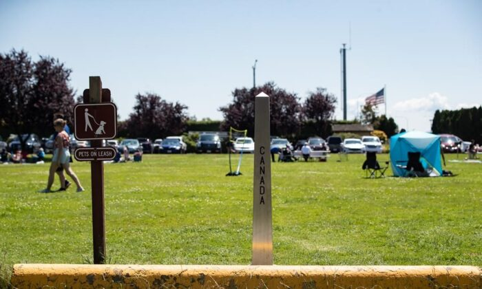 A Canada-U.S. border marker is seen in Surrey, B.C., as people gather at Peace Arch Historical State Park in Blaine, Wash., on July 5, 2020. (Darryl Dyck/The Canadian Press)