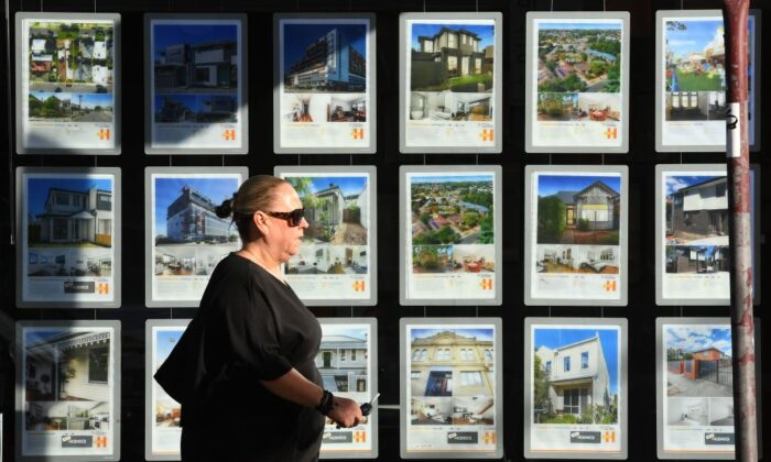 A woman walks past a real estate agent's window advertising houses for sale and auction in Melbourne, Australia on May 1, 2019. (William West/Getty Images)