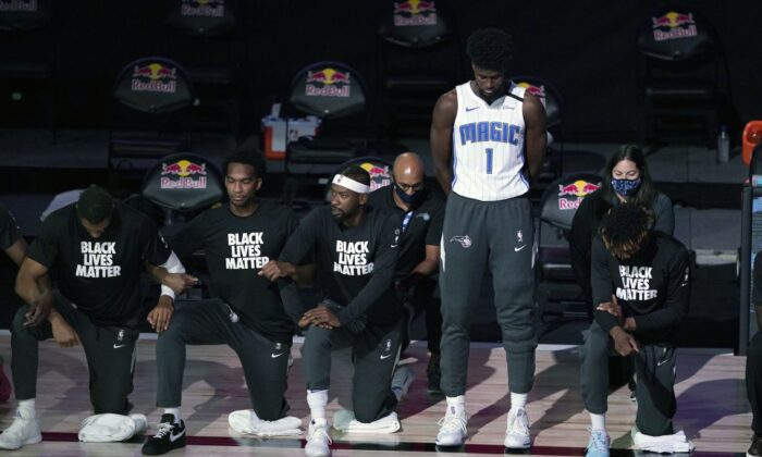 Jonathan Isaac #1 of the Orlando Magic stands as others kneel before the start of a game between the Brooklyn Nets and the Orlando Magic on July 31, 2020. (Ashley Landis - Pool/Getty Images)