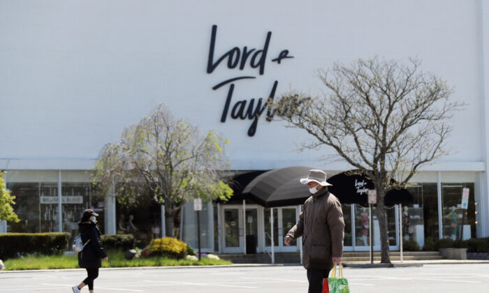 Pedestrians walk past a shuttered Lord and Taylor department store following their filing for bankruptcy amid the COVID-19 pandemic in Garden City, N.Y., on May 12, 2020. (Bruce Bennett/Getty Images)