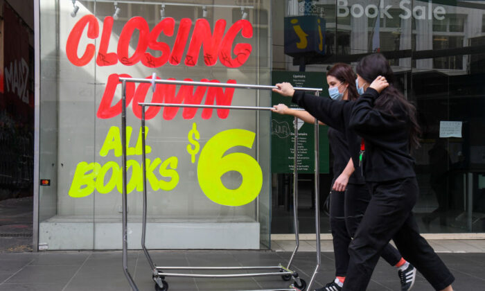 Workers push trolleys past an empty shop in Melbourne's central business district on August 3, 2020 after the state announced new restrictions as the city battles fresh outbreaks of the COVID-19 coronavirus. (William West/AFP via Getty Images)