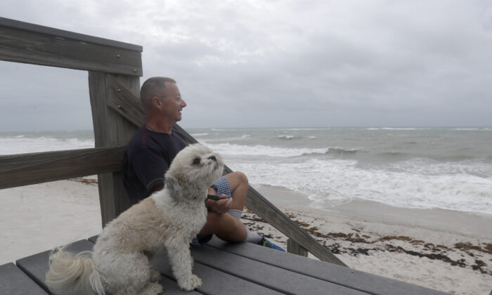 Kent Ahern and his dog Blanco watch waves churned up by Tropical Storm Isaias near Jaycee Beach Park, in Vero Beach, Fla., on Aug. 2, 2020. (Wilfredo Lee/AP Photo)