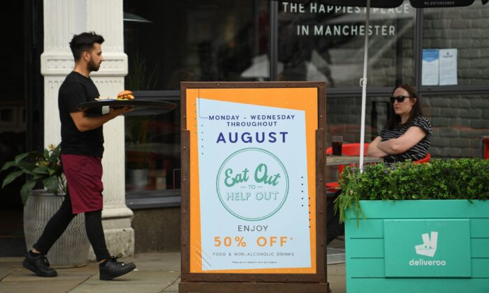 "A server carries food past a sign promoting the British Government's ""Eat Out to Help Out"" scheme to get consumers spending again, outside a restaurant in Manchester, northwest England, on Aug. 3, 2020. (Oli Scarff/AFP via Getty Images)"