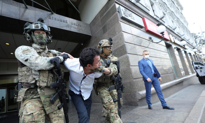 Members of the Security Service of Ukraine (SBU) detain a man who threatened to blow up a bomb in a bank branch, in Kyiv, Ukraine, on Aug. 3, 2020. (The Ministry of Internal Affairs of Ukraine/Handout via Reuters)