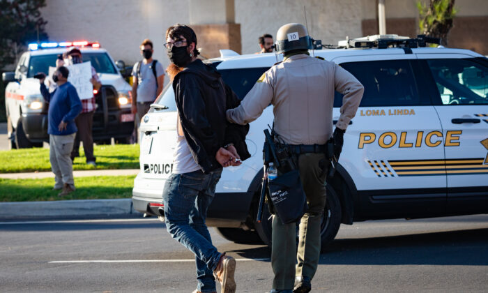 A protester is arrested in Yucaipa, Calif., on Aug. 1, 2020. (John Fredricks/The Epoch Times)