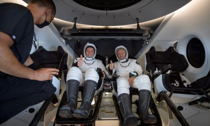 NASA astronauts Robert Behnken (L) and Douglas Hurley are seen inside the SpaceX Crew Dragon Endeavour spacecraft onboard the SpaceX GO Navigator recovery ship shortly after having landed in the Gulf of Mexico off the coast of Pensacola, Fla., on Aug. 2, 2020. (Bill Ingalls/NASA via AP)