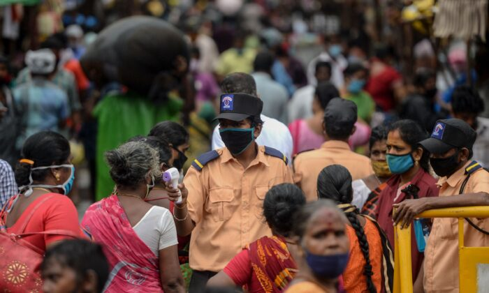 A security personnel (C) checks the body temperature of a woman (C-L) as she enters a market among a crowd of people as a preventive measure against the spread of the COVID-19 coronavirus in Chennai on July 29, 2020. (Arun Sankar/AFP via Getty Images)