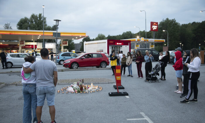 Flowers and candles are placed near where a twelve-year-old girl was shot and killed near a petrol station in Botkyrka, south of Stockholm, Sweden, Aug. 2, 2020. (Ali Lorestani//TT via AP Photo)