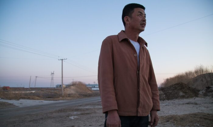 Wang Jianjun stands outside his dairy farm while worrying about the market in Hulunbuir, Inner Mongolia, China on May 1, 2019. (Betsy Joles/ Getty Images)