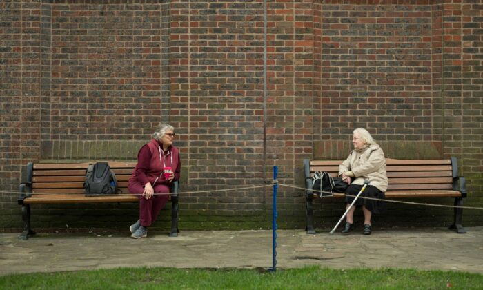 Two women observe social distancing measures as they speak to each other from adjacent park benches amidst the CCP virus pandemic, in the center of York, northern England, on March 19, 2020. (Oli Scarff/AFP via Getty Images)