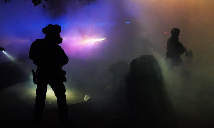 Federal officers stand guard as a protester is arrested in a cloud of tear gas during a protest against racial injustice and police brutality in front of the Mark O. Hatfield U.S. Courthouse in Portland, Oregon, in the early hours of July 30, 2020. (Nathan Howard/Getty Images)