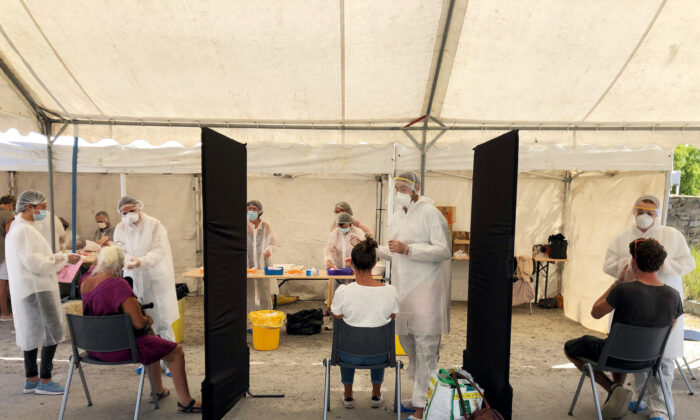 Healthcare workers collect samples in a walk-through test site to detect possible coronavirus infections after the emergence of a cluster of cases due to the illegal opening of the Hacienda Cafe nightclub in Quiberon, France, on July 29, 2020. (Caroline Paillez/Reuters)