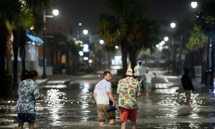 People walk through floodwaters from Hurricane Isaiah on Ocean Blvd in Myrtle Beach, S.C., on Aug. 3, 2020. (Sean Rayford/Getty Images)