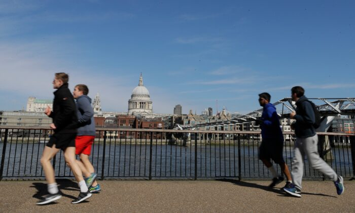 People run to keep fit along the south bank of the River Thames in London, Britain, on March 22, 2020. (Kirsty Wigglesworth/AP Photo)