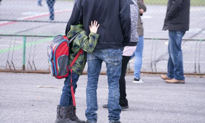 A boy hugs his father as he waits to be called to enter the schoolyard the Marie-Derome School in Saint-Jean-sur-Richelieu, Que. on May 11, 2020. Plans are being made across the country for how to safely send students back to school in the fall as the COVID-19 pandemic continues. (Paul Chiasson/ The Canadian Press)