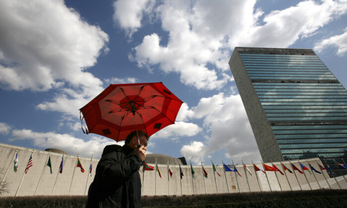 A man holding an umbrella passes the UN Headquarters in New York, on March 24, 2008. (Mike Segar/Reuters)