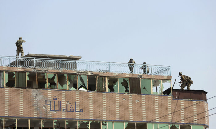 Afghan security personnel take position on top of a building where insurgents are hiding, in the city of Jalalabad, Afghanistan, on Aug. 3, 2020.  (AP Photo/Rahmat Gul)