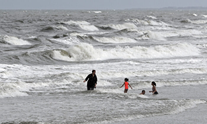 People swim in the ocean as Tropical Storm Isaias approaches in Kure Beach, N.C., on Aug. 3, 2020. (Gerry Broome/AP Photo)