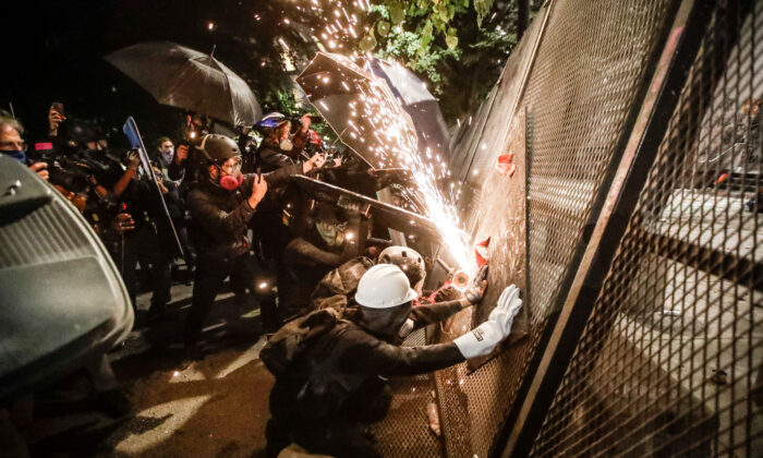 Rioters try to cut through a steel fence at the Mark O. Hatfield U.S. Courthouse in Portland, Ore., on July 24, 2020. (Marcio Jose Sanchez/AP Photo)