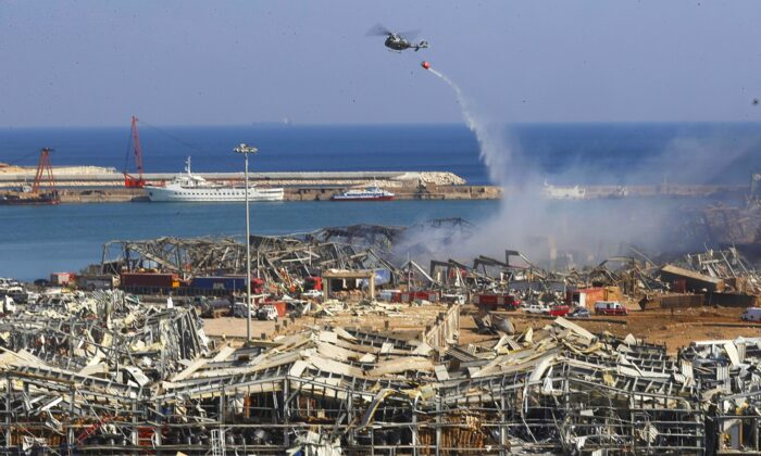 A Lebanese army helicopter throw water at the scene where an explosion hit the seaport of Beirut, Lebanon on Aug. 5, 2020. (Hussein Malla/AP Photo)