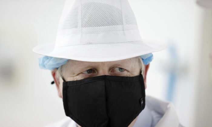 Britain's Prime Minister Boris Johnson wearing a black face mask with the number 10 , at Orkney Cheese in Kirkwall, during a visit to the Highlands and Northern Isles of Scotland, on July 23, 2020. (Robert Perry/PA via AP Photo)