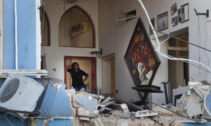 A woman stands inside a damaged restaurant a day after an explosion hit the seaport of Beirut, Lebanon on Aug. 5, 2020.  (AP Photo/Hussein Malla)