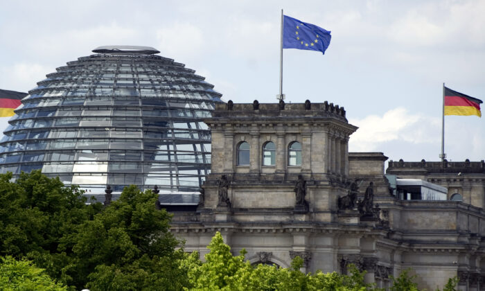 A European Union flag and a German national flag fly over the Reichstag building in Berlin, Germany, on May 25, 2011. (Johannes Eisele/AFP via Getty Images)