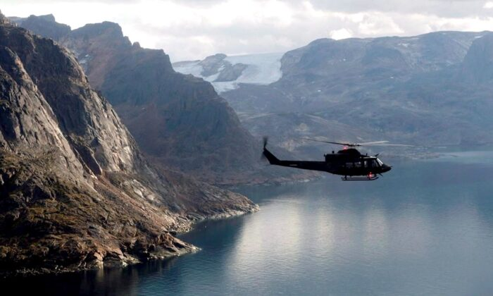 A Canadian military Griffon helicopter flies along the shoreline of Baffin Island as it moves personnel between Operation Nanook and Iqaluit, on Aug. 26, 2014. (Adrian Wyld/The Canadian Press)