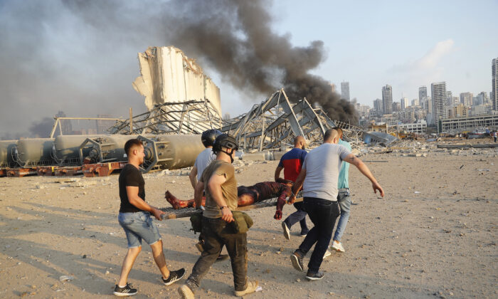 Civilians carry a victim at the explosion scene that hit the seaport, in Beirut Lebanon, on Aug. 4, 2020. (Hussein Malla/AP Photo)
