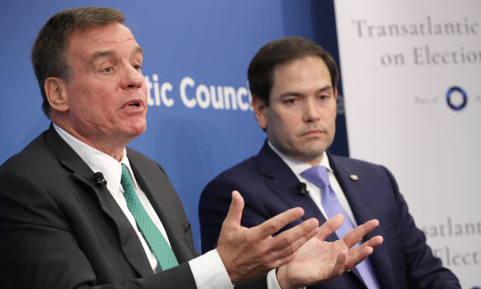 Sen. Mark Warner (D-Va.) (L) and Sen. Marco Rubio (R-Fla.), both members of the Senate Intelligence Committee, participate in a discussion at the Atlantic Council in Washington on July 16, 2018. (Chip Somodevilla/Getty Images)