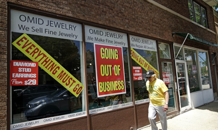 A man walks past a retail store that is going out of business due to the coronavirus pandemic in Winnetka, Ill., on June 23, 2020. (Nam Y. Huh/AP Photo)