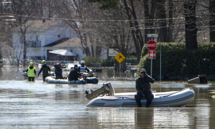 An operation to rescue pets from homes that had to be abandoned during evacuations is underway on a flooded street in the Montreal suburb of Sainte-Marthe-sur-le-Lac, Quebec, on April 29, 2019. (SEBASTIEN ST-JEAN/AFP via Getty Images)