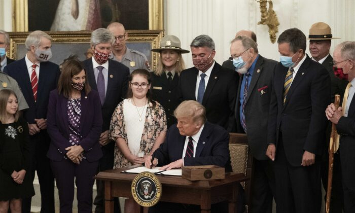President Donald Trump signs the Great American Outdoors Act during a singing ceremony in the East Room of the White House in Washington on Aug. 4, 2020. (Drew Angerer/Getty Images)