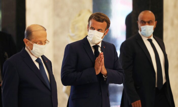 French President Emmanuel Macron and Lebanon's President Michel Aoun wear protective face masks as they meet following Tuesday's blast in Beirut's port area, at the presidential palace in Baabda, Lebanon, on Aug. 6, 2020. (Mohamed Azakir/Reuters)