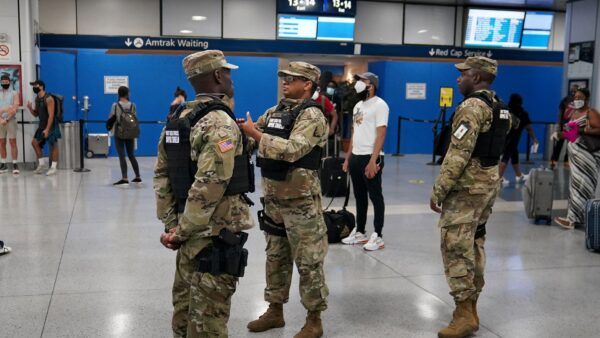 Military officials stand at Penn Station