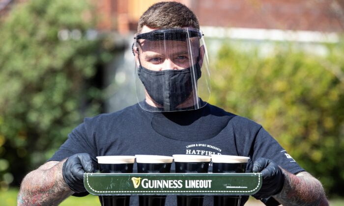 Harry McKeaveney from The Hatfield House bar, wearing a face mask and gloves, poses for a photograph as he delivers pints of Guinness to customers' front doors, in Belfast, Northern Ireland, on April 16, 2020. (Paul Faith/AFP via Getty Images)
