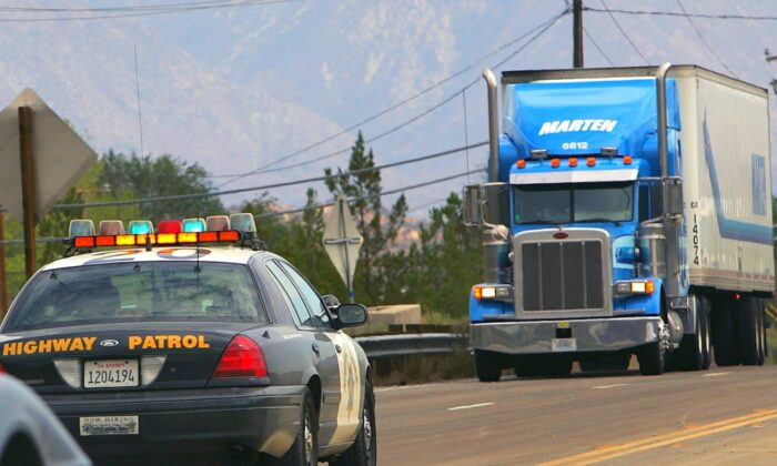 A trucker approaches a highway patrolman in a file photo taken near Wrightwood, California, 50 miles northeast of Los Angeles on July 23, 2007. (David McNew/Getty Images)