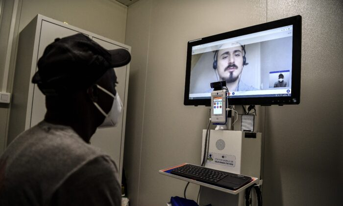 Malian migrant worker Tidjane (L) wearing a protective face mask attends a teleconsultation on suspicion of COVID-19, at a special medical unit set up outside a building housing migrant workers as part of a private initiative supported by the Paris city hall and aimed at identifying sick people among a vulnerable population, in Paris on May 8, 2020. (Christophe Archambault/AFP via Getty Images)