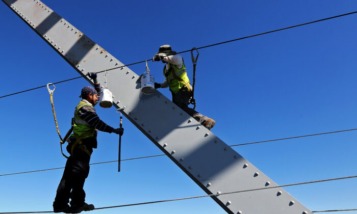 File photo of workers painting the Julien Dubuque Bridge along U.S. 20 in Dubuque, Iowa, on Aug. 24, 2015. (Dave Kettering/Telegraph Herald via AP)