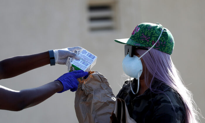 A school faculty member passes out food to family of a student in Oakland, Cali., on March 19, 2020.  (Justin Sullivan/Getty Images)