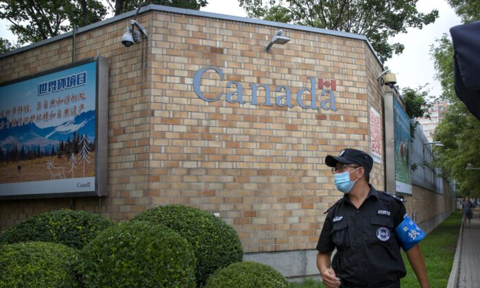 A security officer stands outside the Canadian Embassy in Beijing on Aug. 6, 2020. (AP Photo/Mark Schiefelbein)