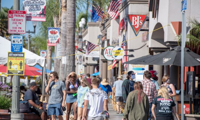 People browse restaurants and shops in downtown Huntington Beach, Calif., on July 16, 2020. (Robin Beck/AFP via Getty Images)