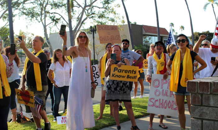 Parents hold signs and cell phones at a gathering to protest mandated school closures amid the COVID-19 pandemic in Santa Ana, Calif., on Aug. 4, 2020. (Jamie Joseph/The Epoch Times)